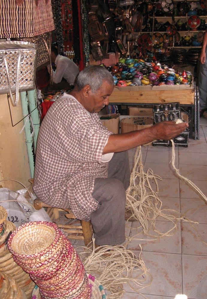 uomo che intreccia corda al mercato di Marrakech